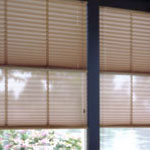 Rectangular pleated window shades rise from the bottom and stack at the tip.