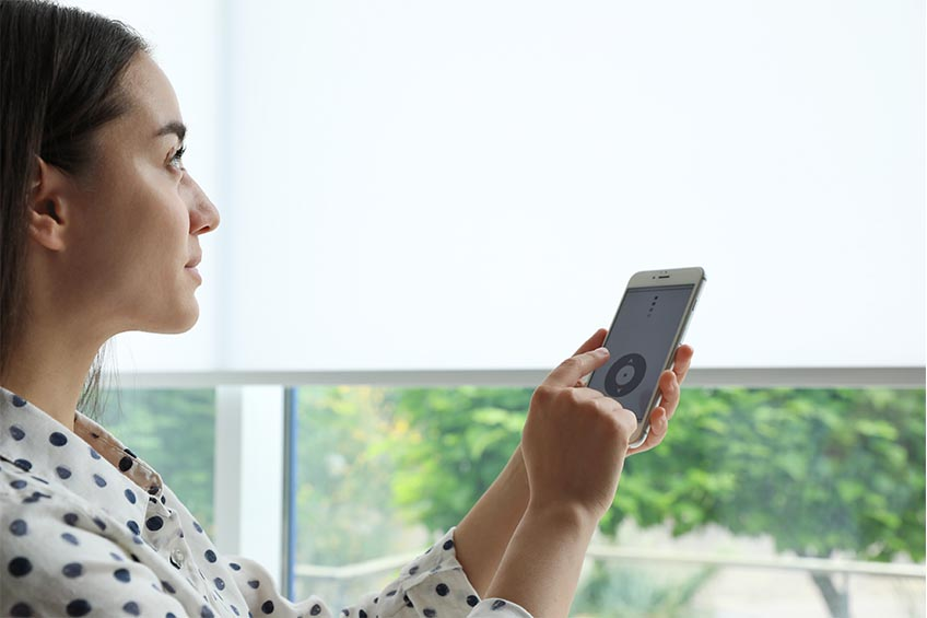 woman controlling blinds with her mobile device