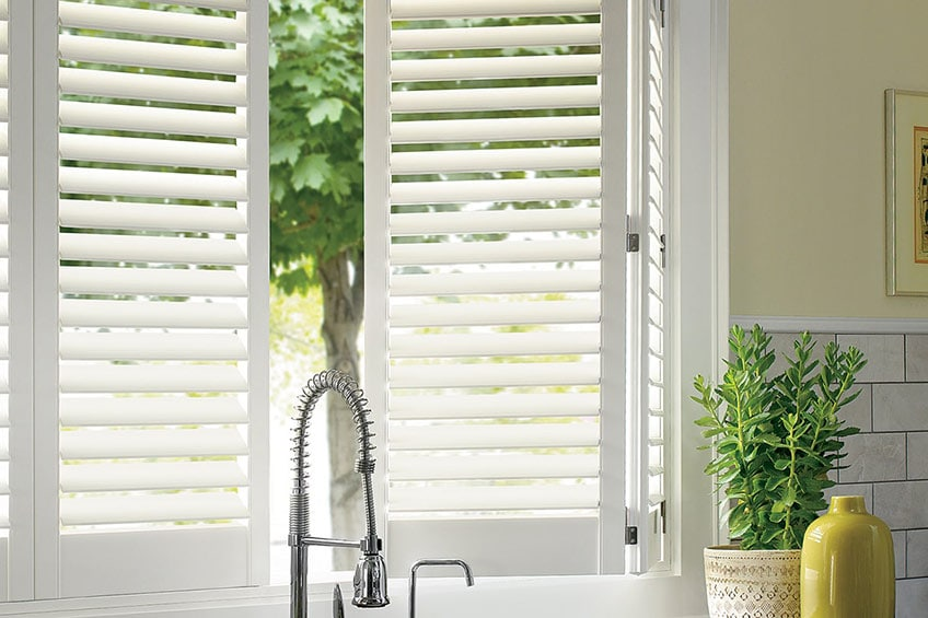 sunshine coming through a kitchen window with white plantation shutters