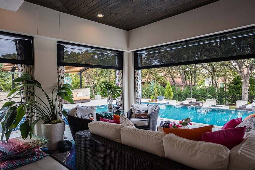 outdoor patio next to pool with motorized screens
